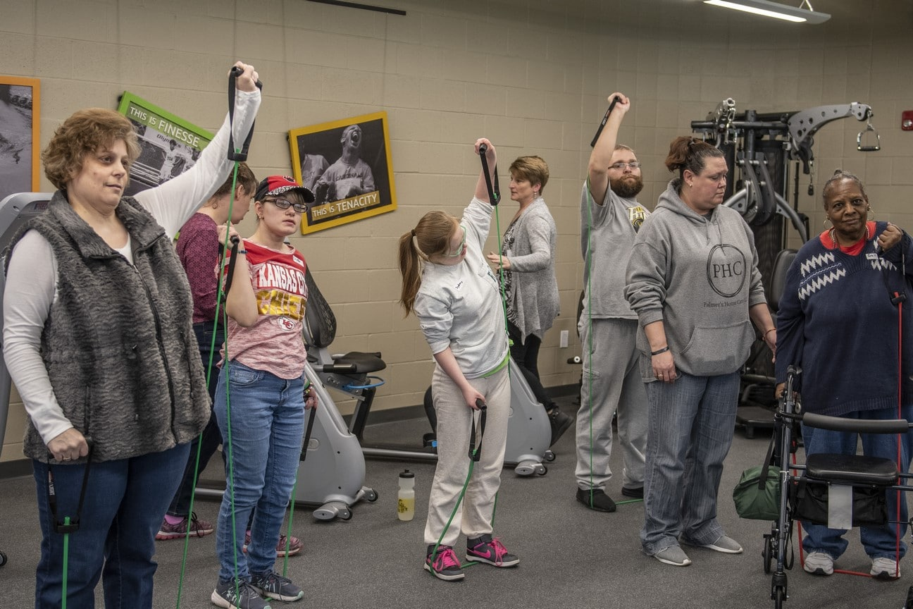 A group of 10 athletes use workout bands in the fitness center of the Training for Life Campus