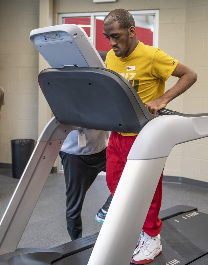 An athlete receives instruction from a volunteer on how to use a treadmill in the fitness center of the Training for Life Campus