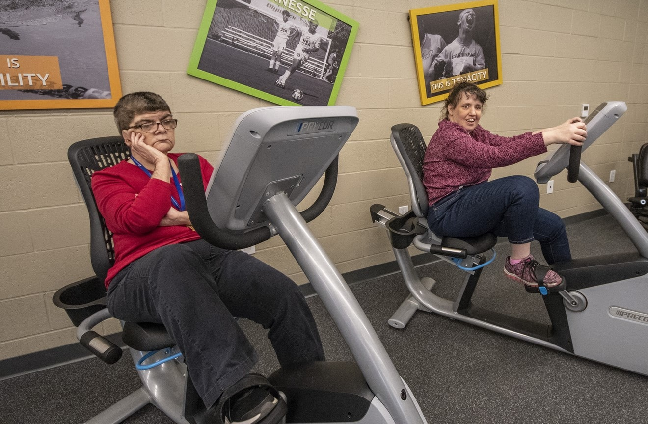 Two athletes work out on stationary bikes in the fitness center at the Training for Life Campus