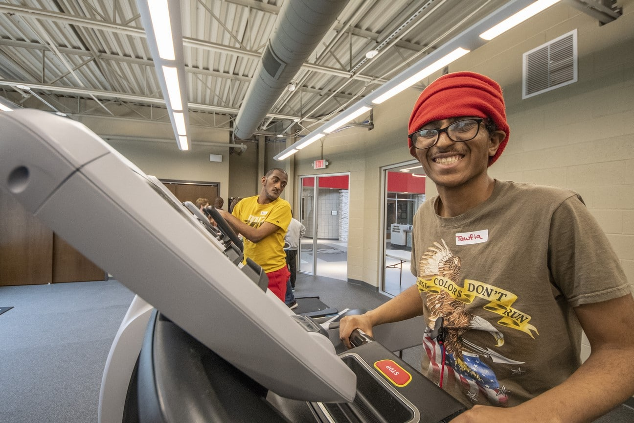 An athlete walking on a treadmill smiles big for the camera
