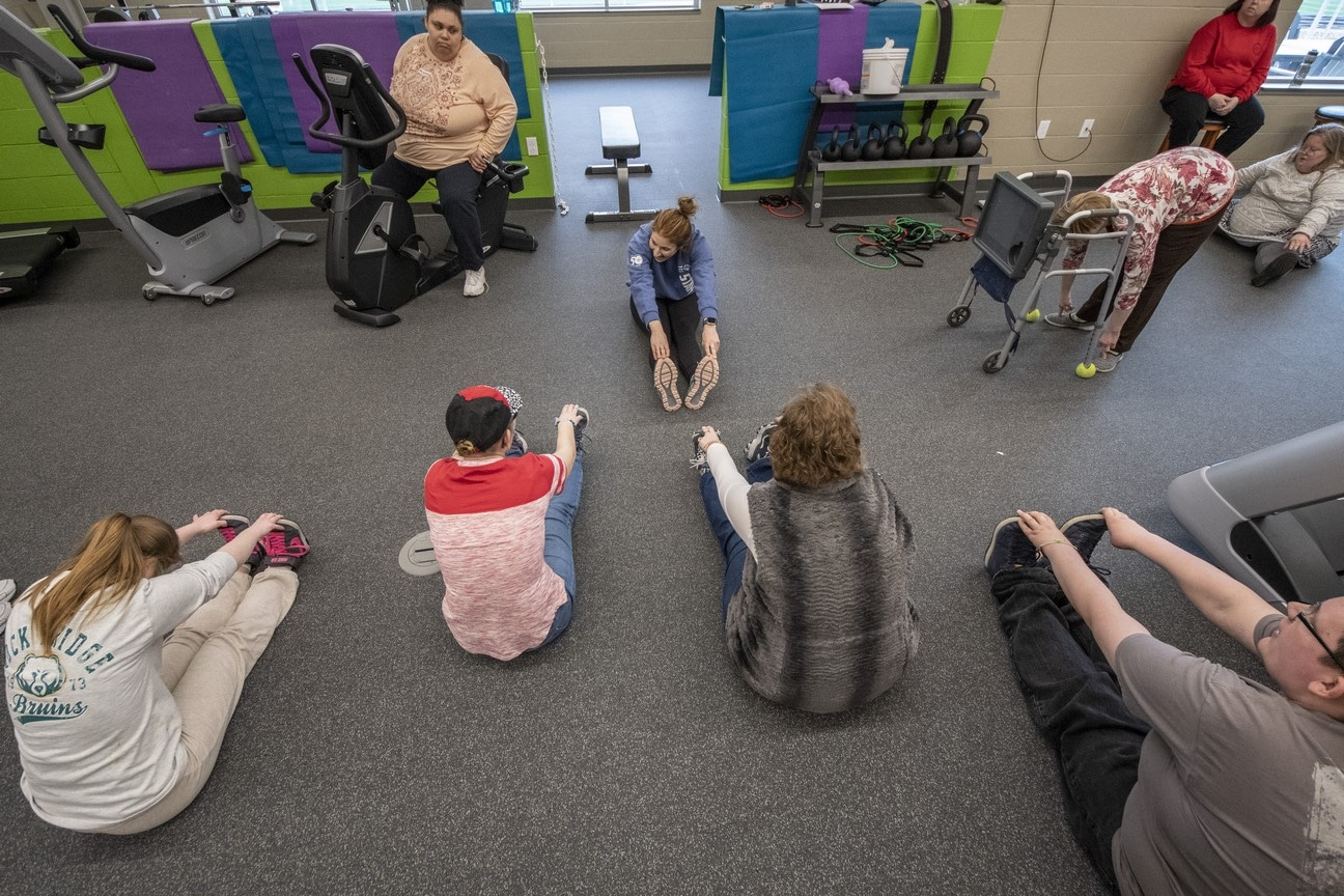 A volunteer sits on the ground and leads a lesson on stretching for a group of athletes