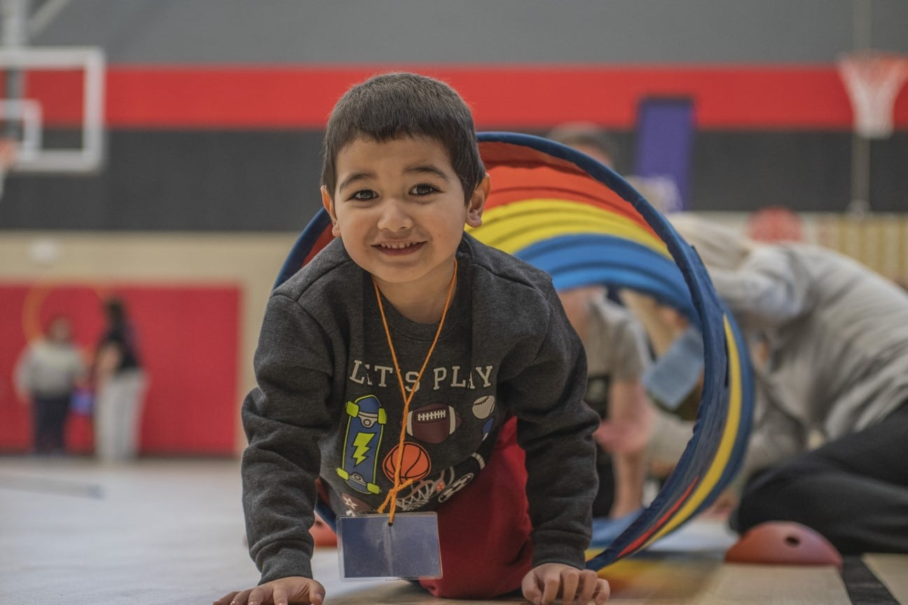 A Young Athlete smiles at the camera as they move through a play tunnel