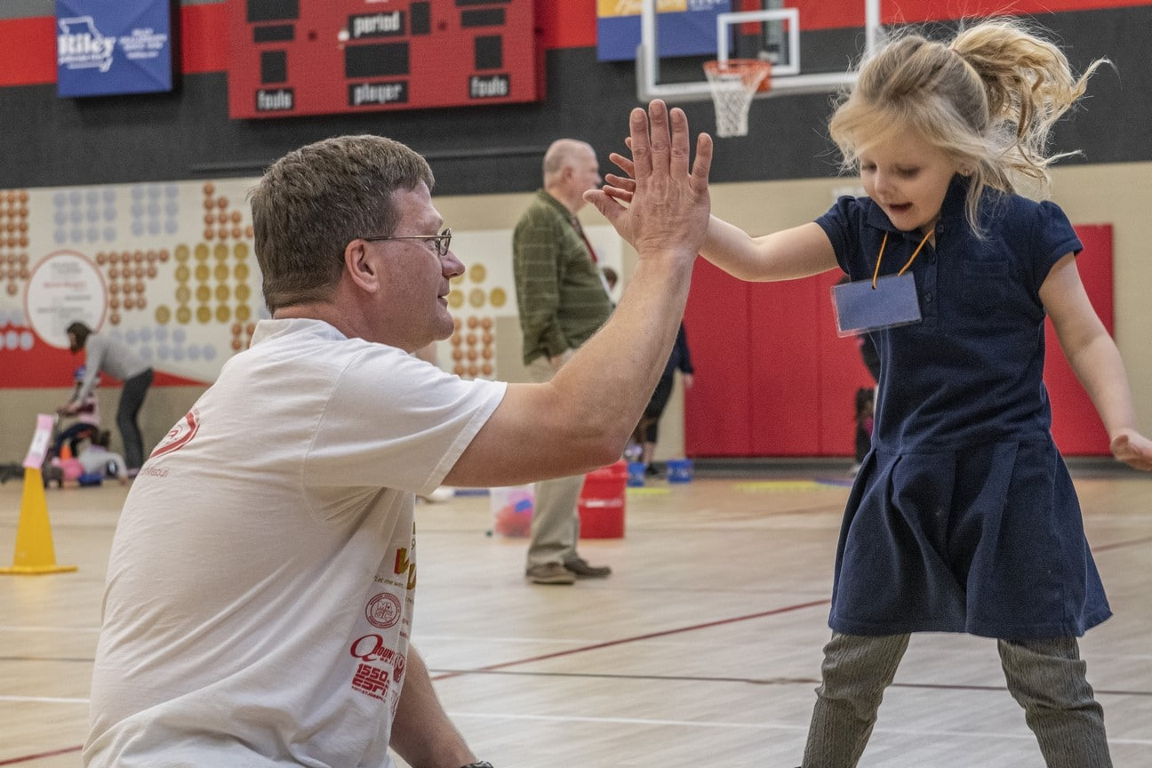 A Young Athlete jumps in the air and high-fives a volunteer