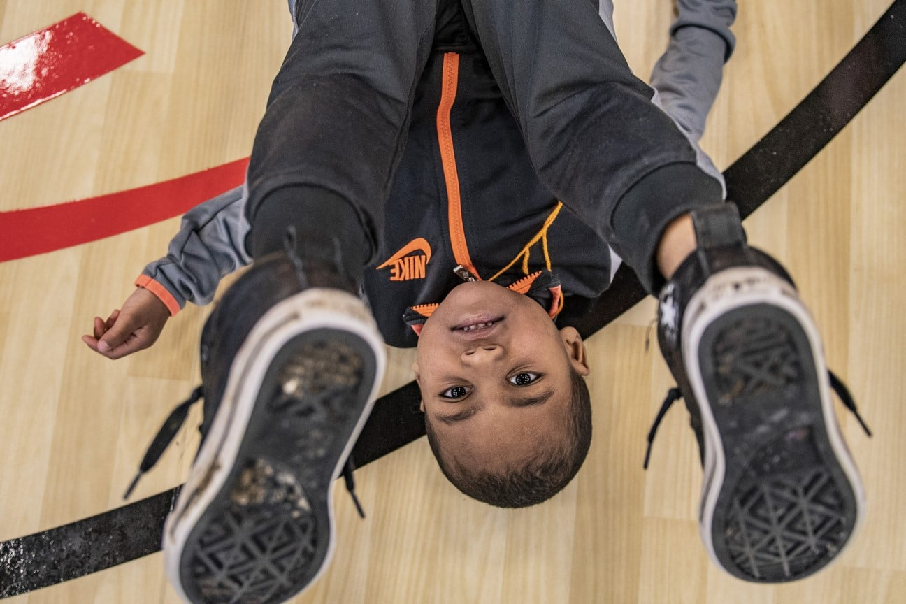 A Young Athlete lies on their back with their feet in the air while smiling at the camera