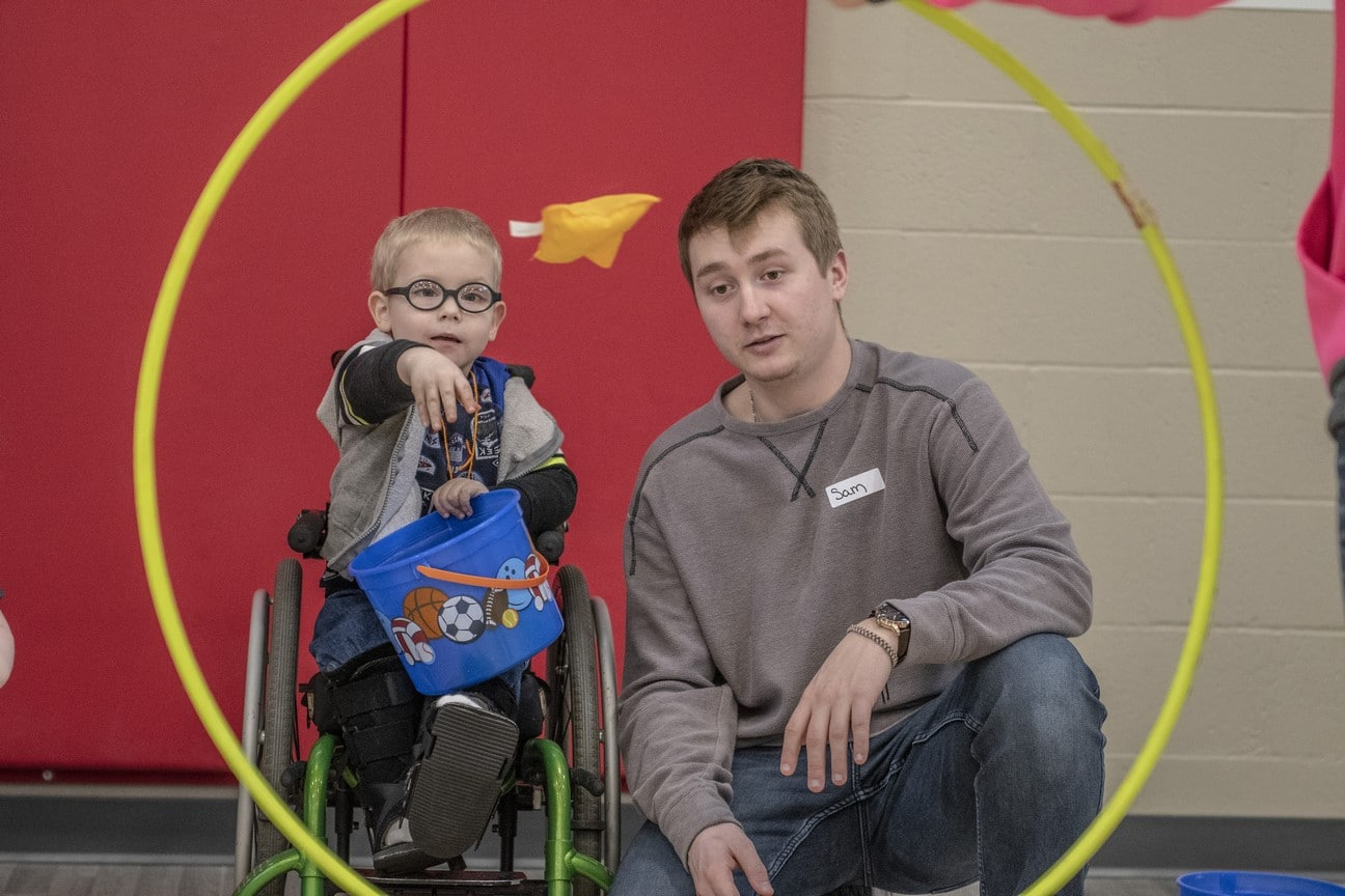 A Young Athlete using a wheelchair throws a bean bag through a hula hoop as a volunteer looks on