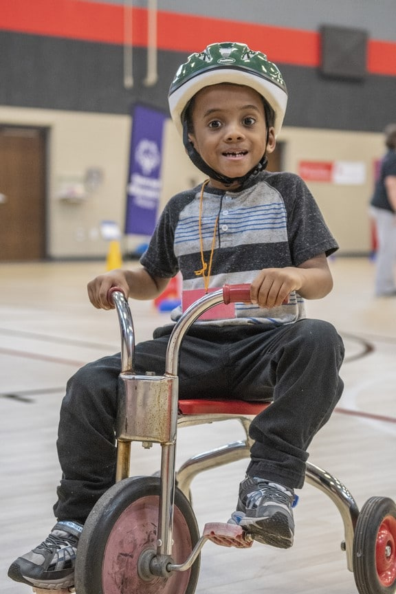A Young Athlete rides a tricycle and smiles at the camera