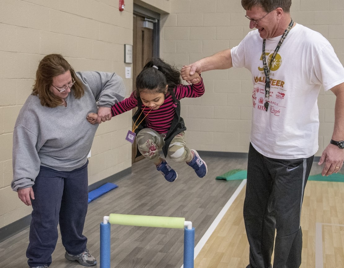 Two volunteers hold the hands of a Young Athlete and help them jump over an obstacle