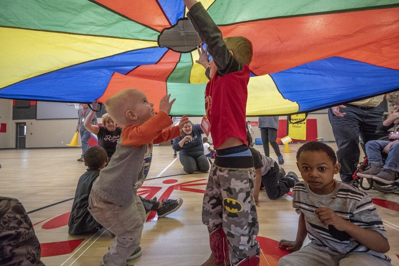 A group of Young Athletes jump for joy underneath a rainbow parachute