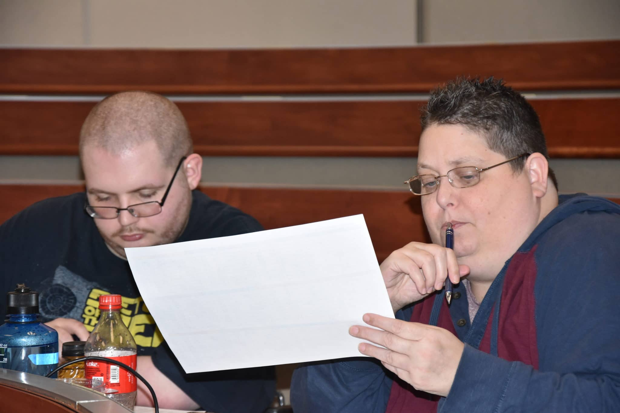 A mentor looks at a piece of a paper while their athlete-leader studies their notes during an Athlete Leadership class