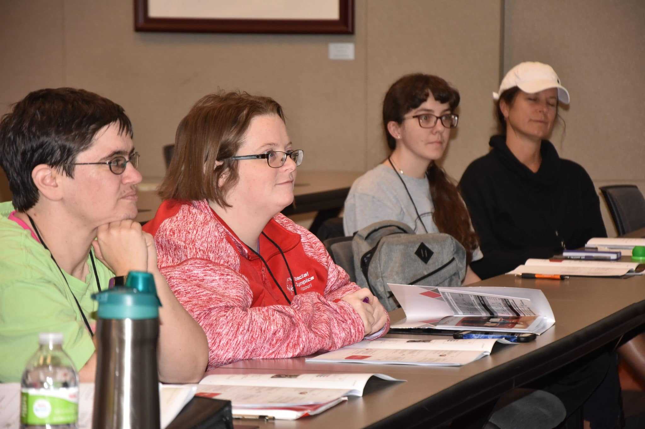 Two athlete-leaders and two mentors pay attention during an Athlete Leadership class