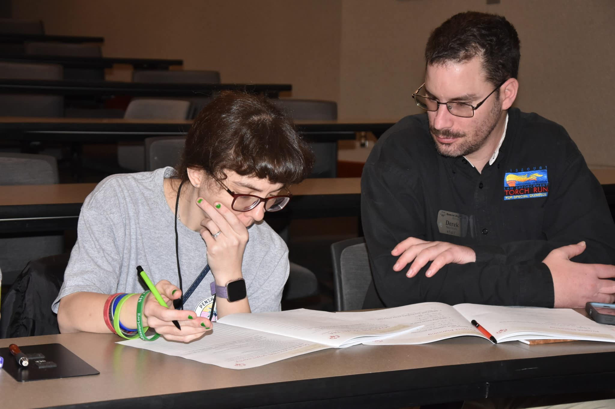 An instructor watches over an athlete-leader as they write a speech