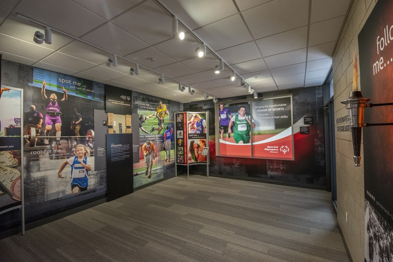 An interior photo of the Hall of Inspiration at the Training for Life Campus with athlete pictures and a torch hanging on the wall