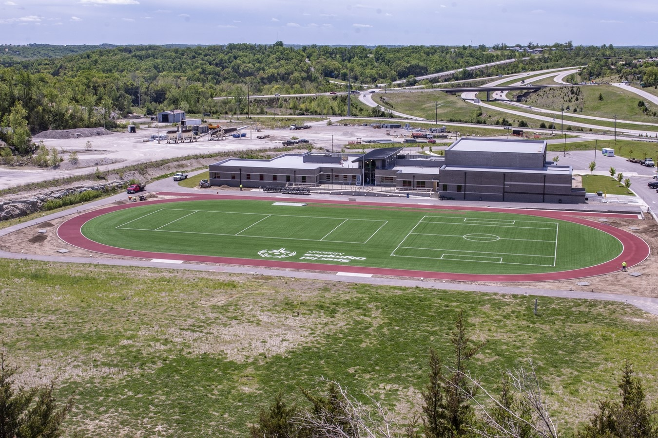 An aerial photo of the back part of the Training for Life Campus showing the track, turf field, and open space