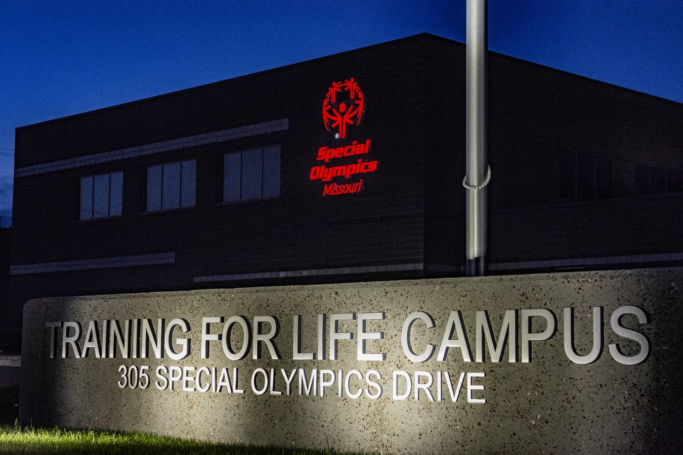 An exterior nighttime photo of the sign lit up at the Training for Life Campus