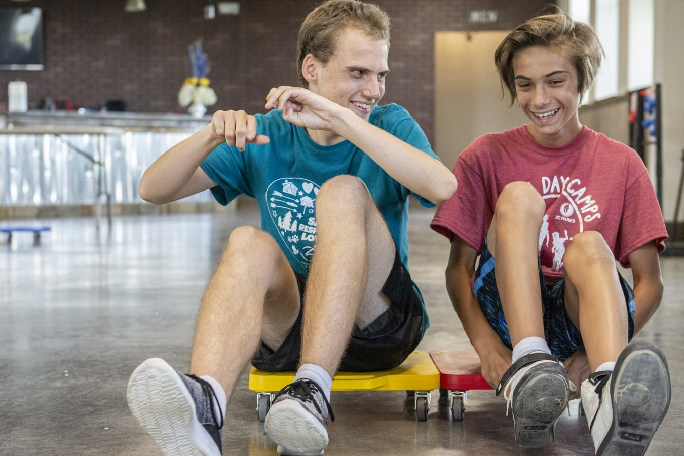 Athlete and volunteers smile as they sit on square scooter boards