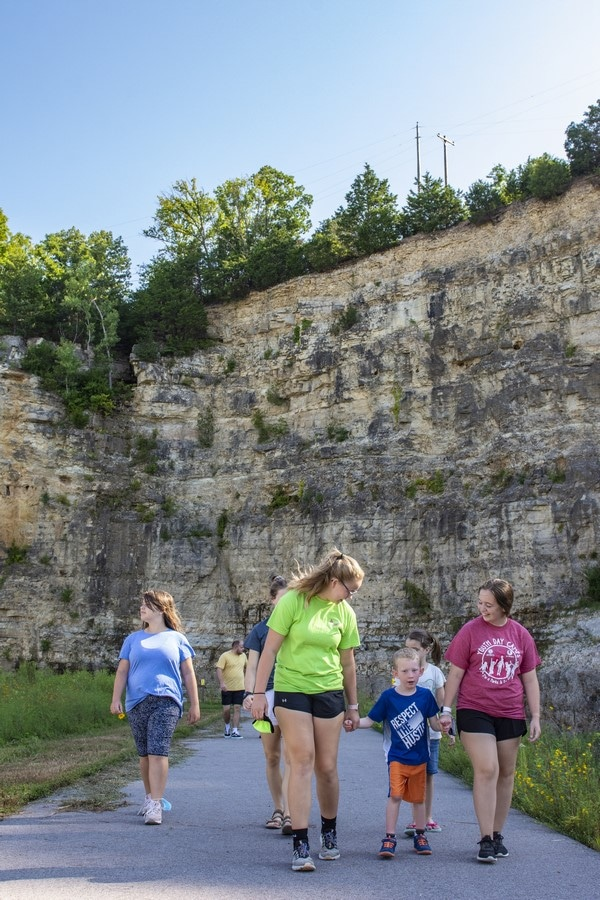 Young athletes and volunteers hold hands while walking on the SOMO walking trail