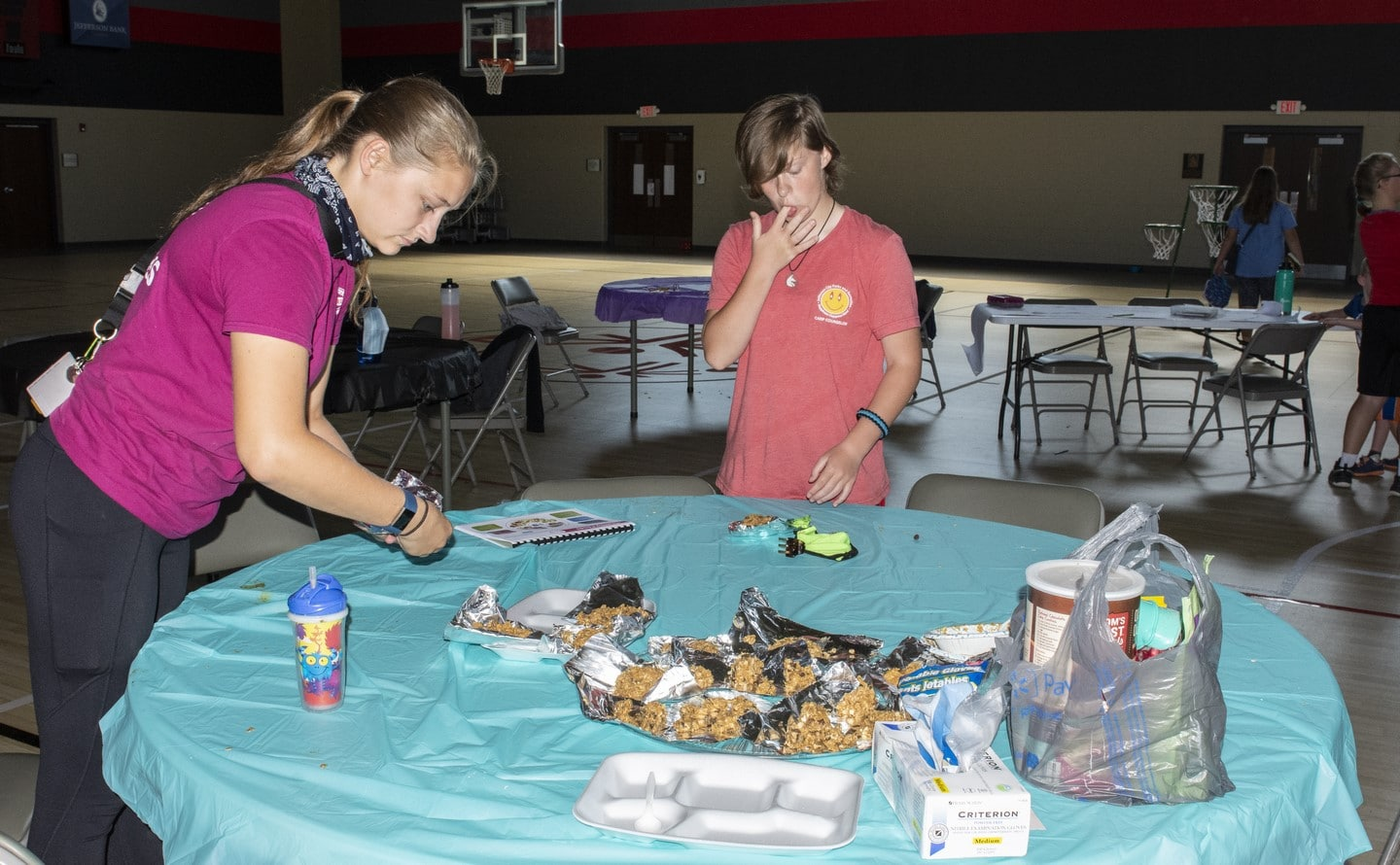 A volunteer and an athlete make snacks