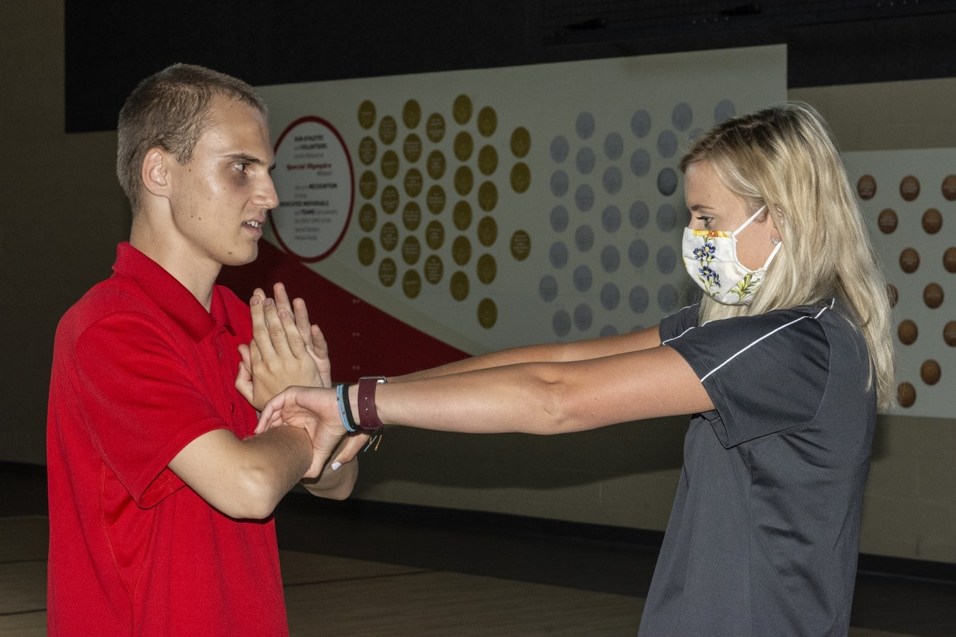 A volunteer helps an athlete stretch their arm muscles
