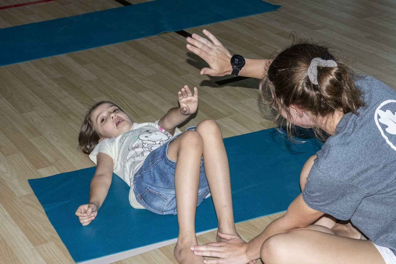 A Young Athlete lies on a mat and tries to do a sit-up while a volunteer holds their feet down