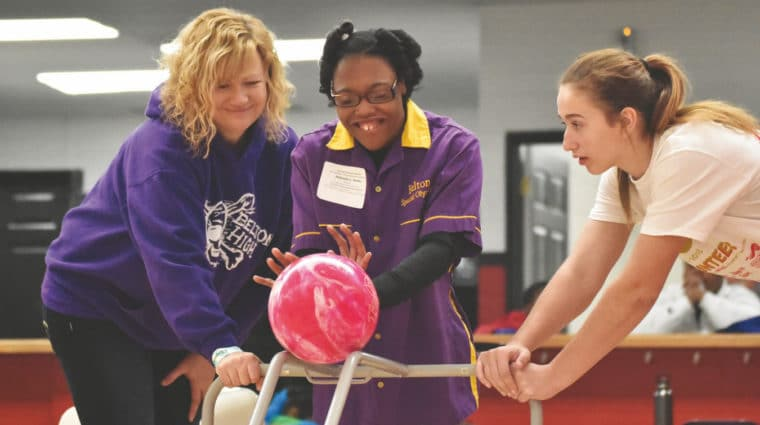 An athlete pushes a pink bowling ball down a ramp while flanked by volunteers on either side