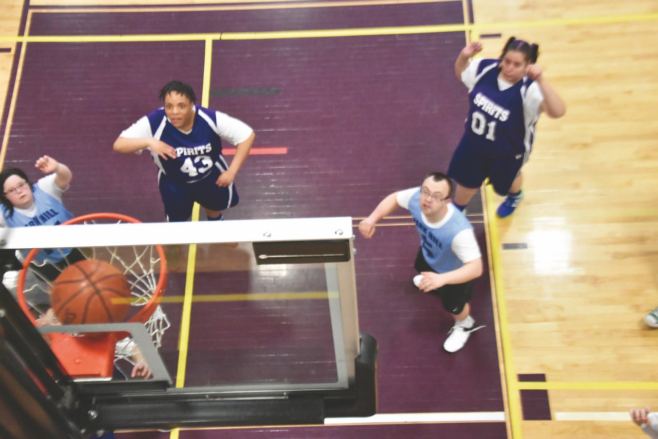 A top-down photo showing athletes on a basketball court watching the ball go into the hoop