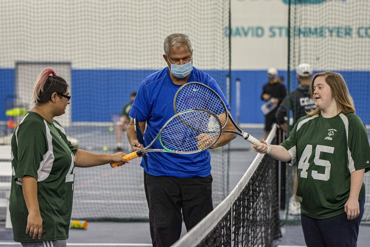 Two athletes meet at the tennis net to high-five tennis rackets while volunteers watches