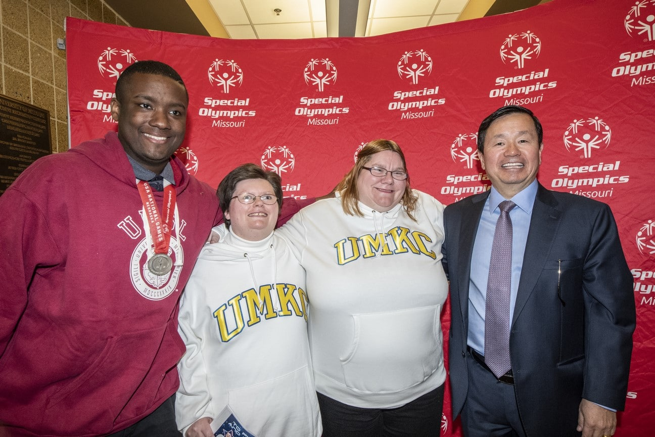 Three athletes pose for a photo with a donor