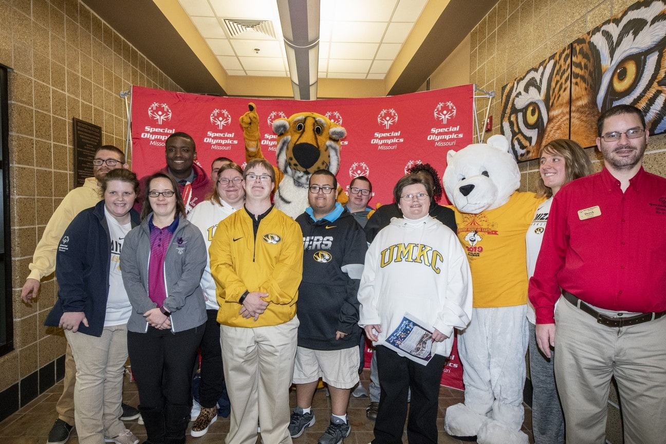 A group of a dozen athletes pose for a photo with a person in a Truman the Tiger costume