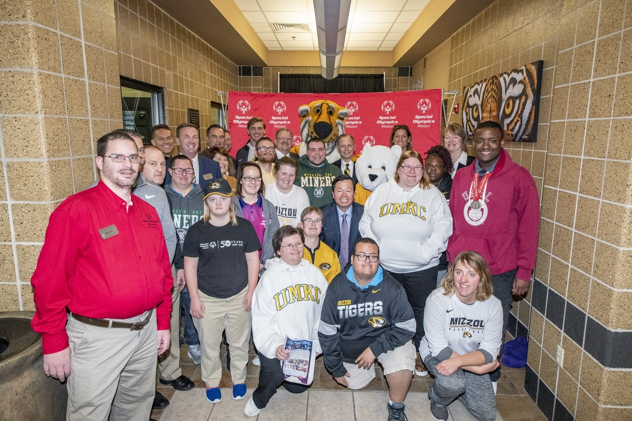 A large group of athletes, volunteers, and supporters pose for a photo with someone in a Truman the Tiger outfit