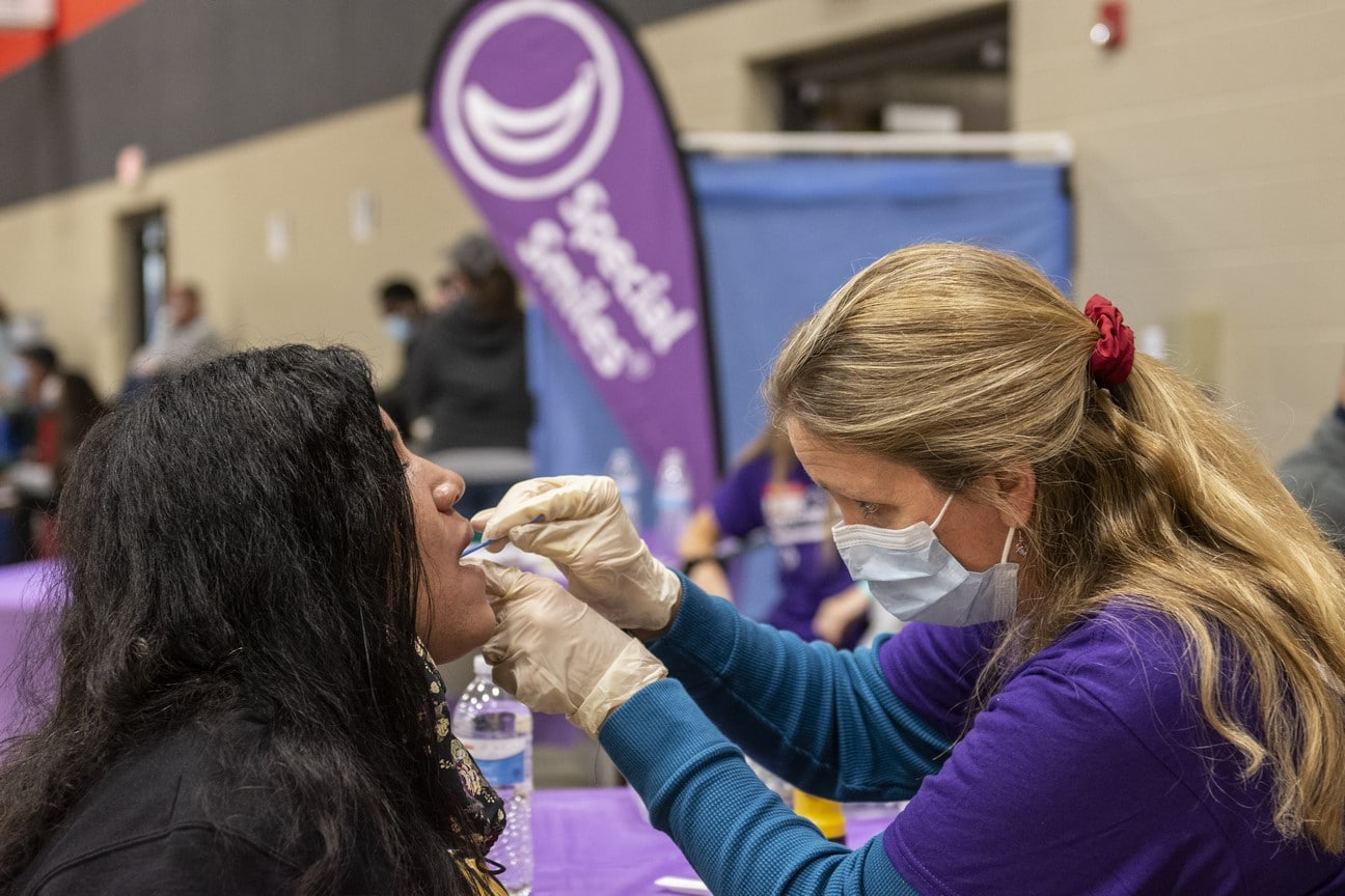 A health professional sticks a mirror in an athlete's mouth during a dental exam