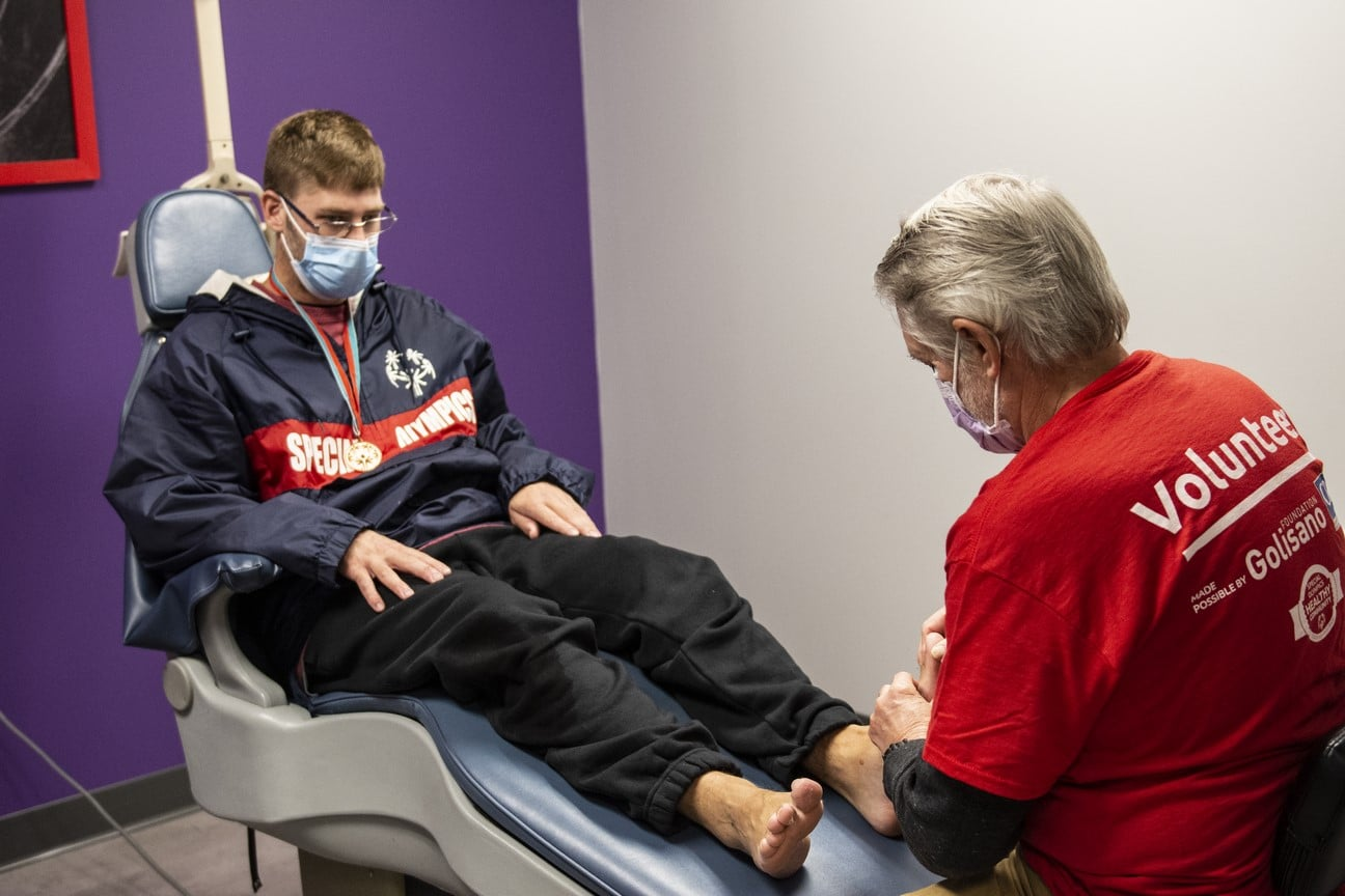 A health professional inspects the feet of an athlete