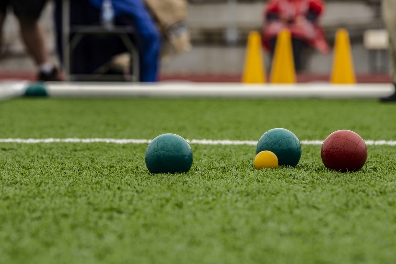 Bocce balls rest on a turf field nestled around the pallina