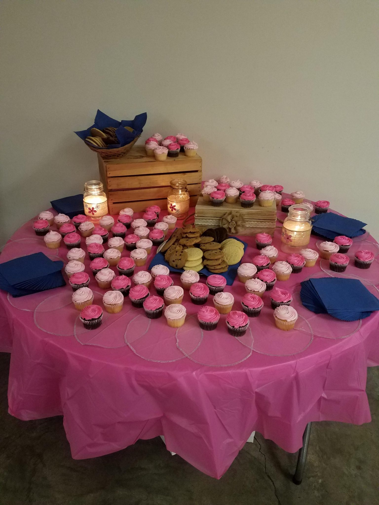A collection of cookies and pink cupcakes sit on a table