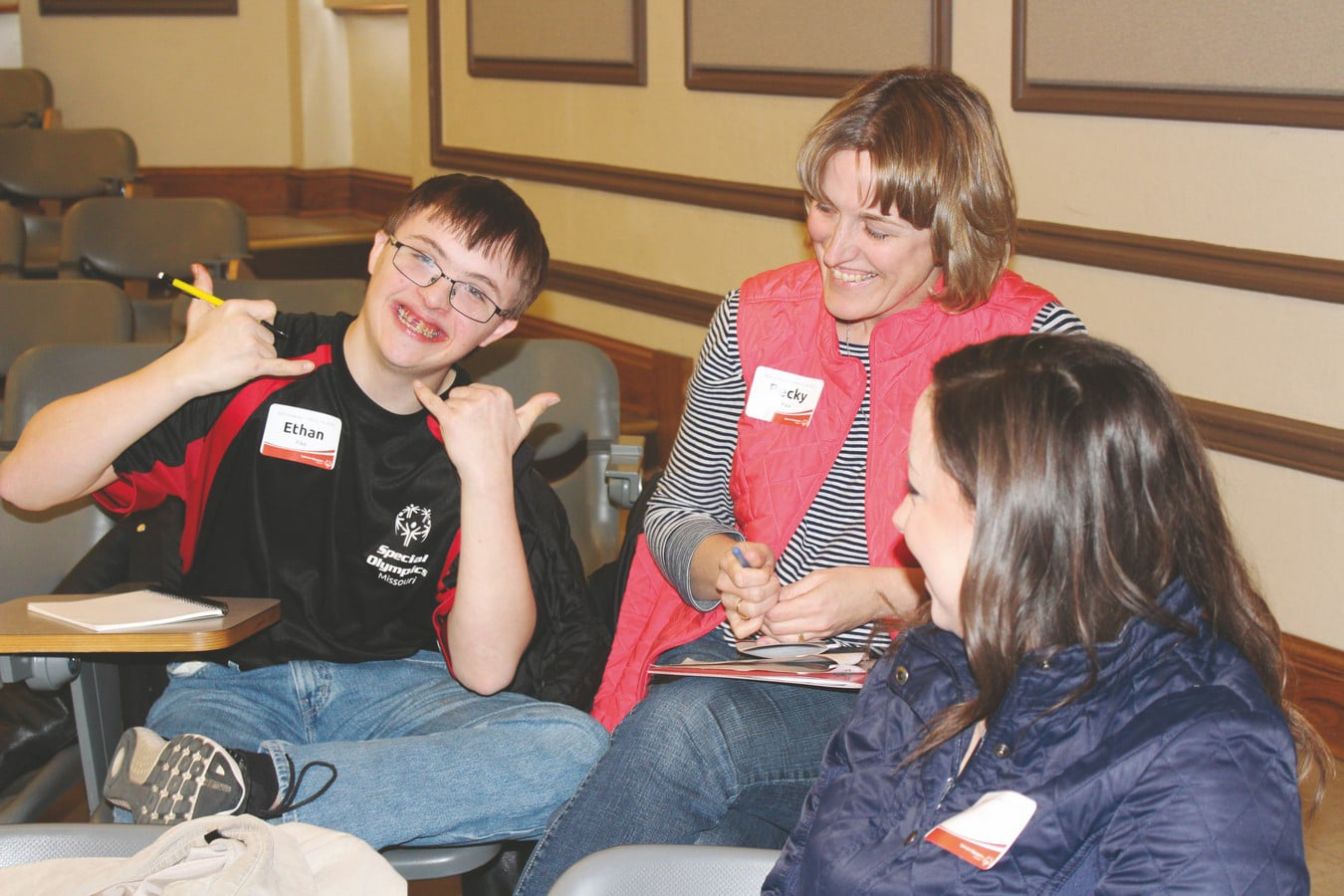 An athlete-leader looks at and smiles for the camera during an Athlete Leadership class while their mentor looks on and smiles