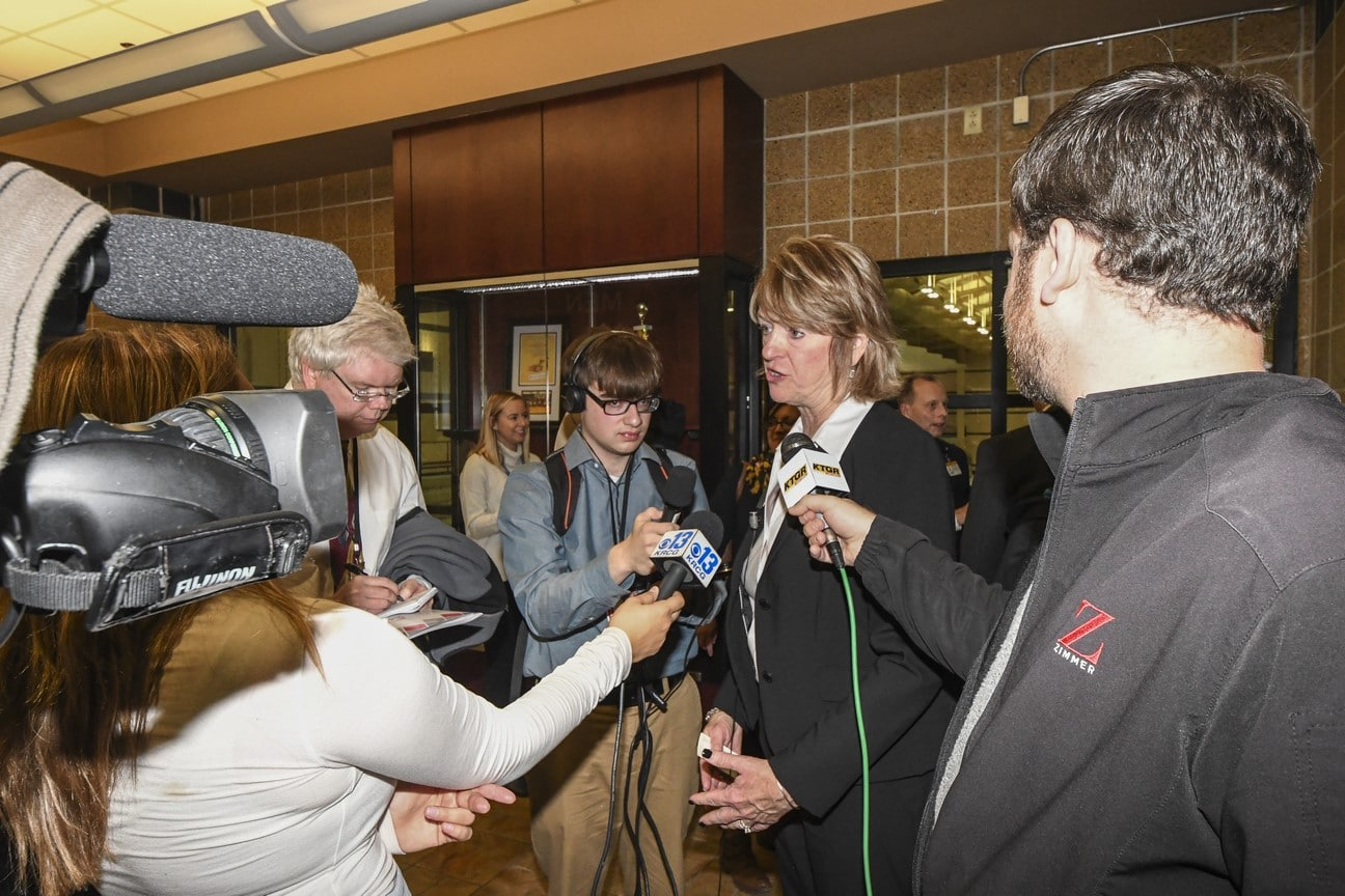 A group of reporters hold microphones and ask questions