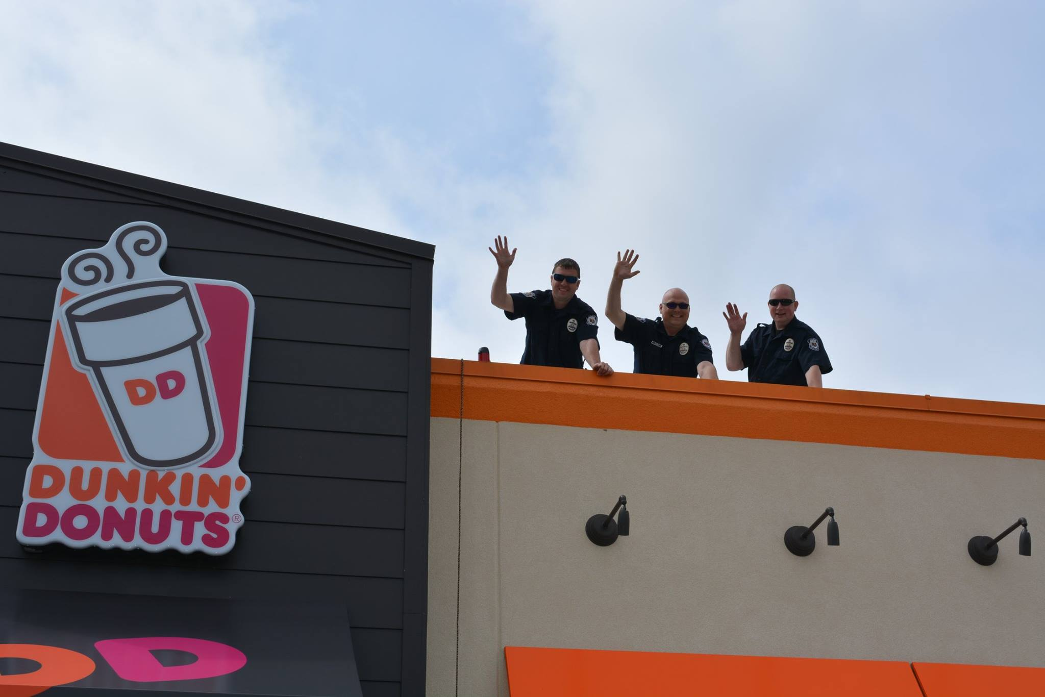 Three law enforcement officers stand on the roof of a Dunkin' Donuts and wave