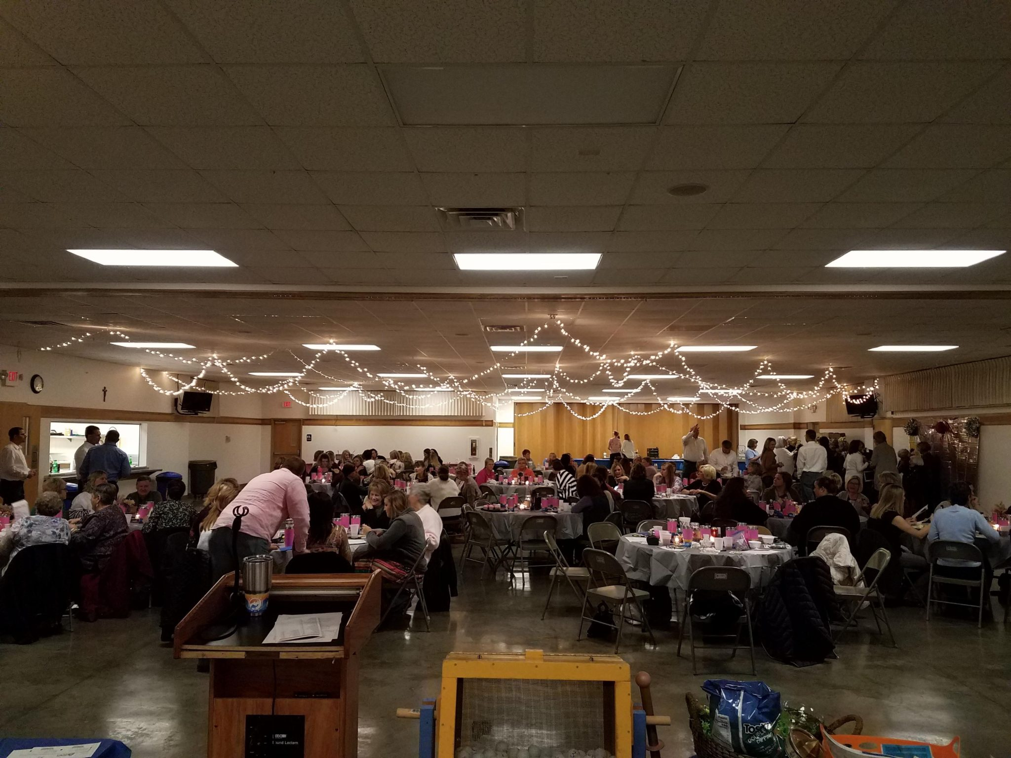 A large gathering with people sitting at tables and string lights hanging from the ceiling