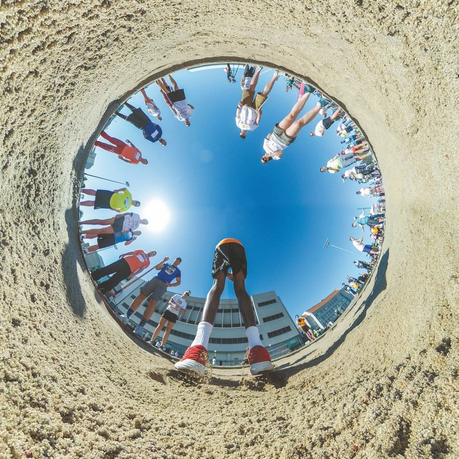 """A 360-degree photo in """"little planet"""" form that shows an athlete jumping into a sand pit with volunteers gathered around"""