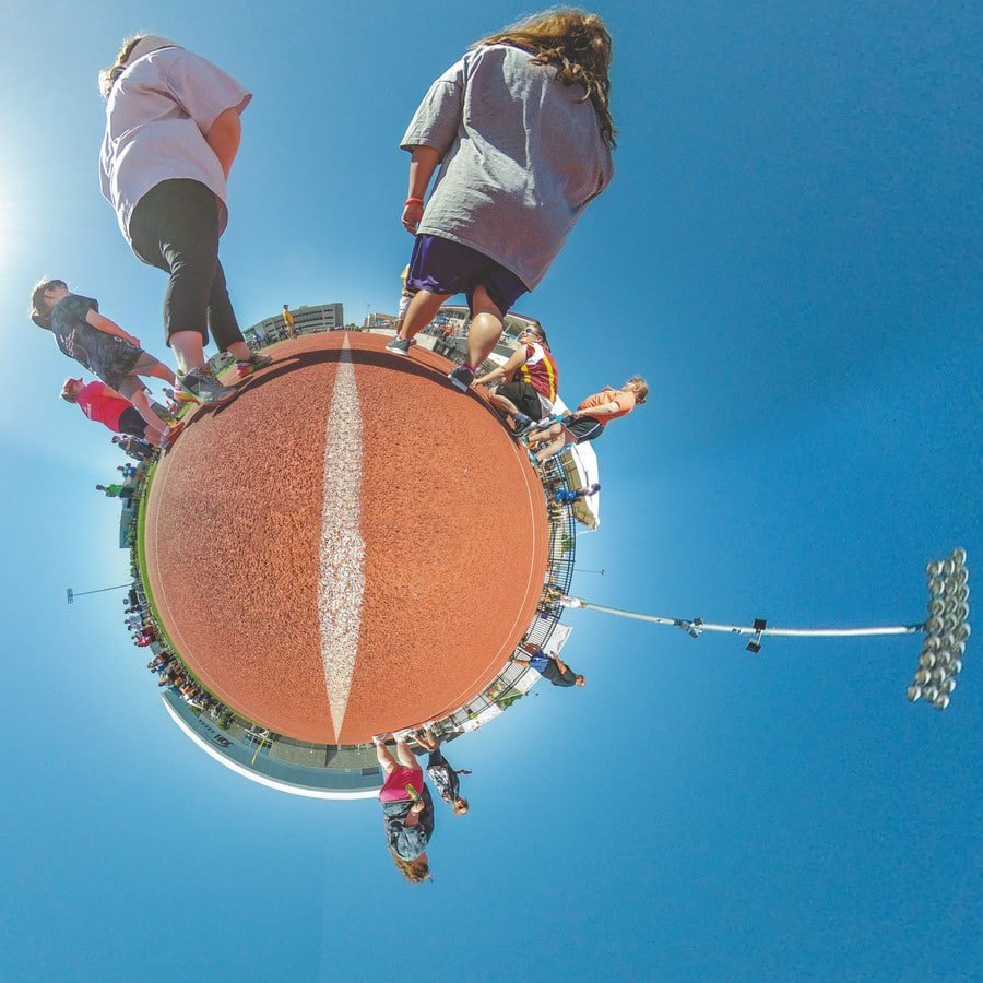 """A 360-degree photo in """"little planet"""" form that shows athletes on a track"""