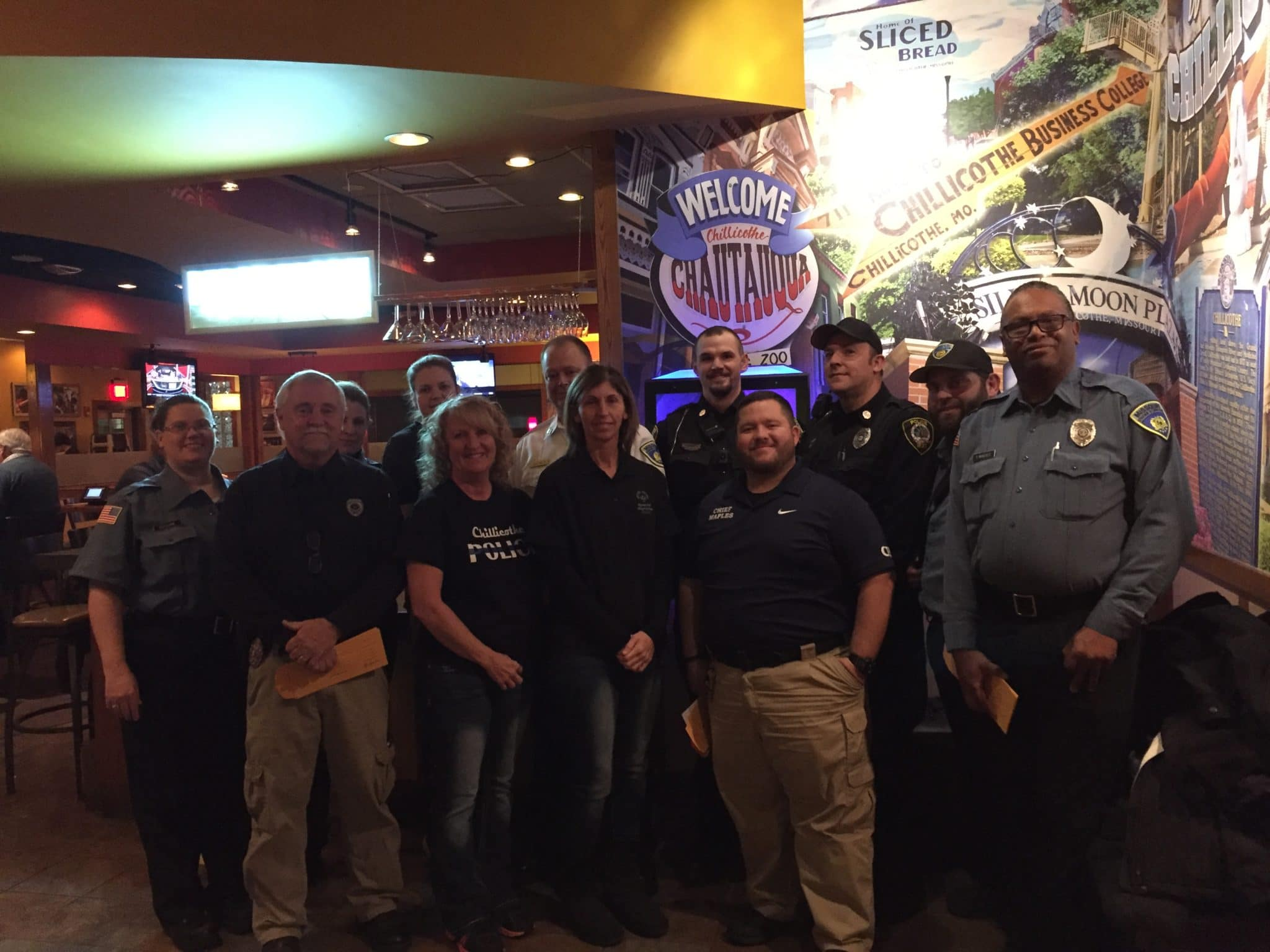 A group of law enforcement officers and servers pose for a photo in a restaurant
