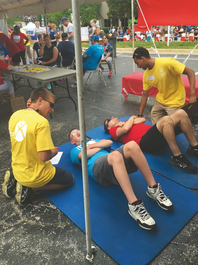 Two athletes lie on the ground and do sit-ups while two volunteers look on
