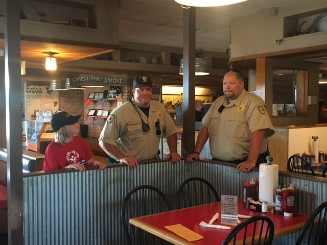 Two law enforcement officers stand next to an athlete in a restaurant