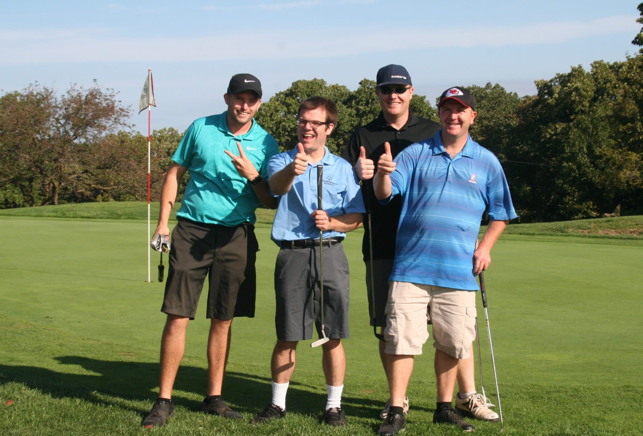 A group of golfers pose on a green by smiling at the camera and putting their thumbs in the air