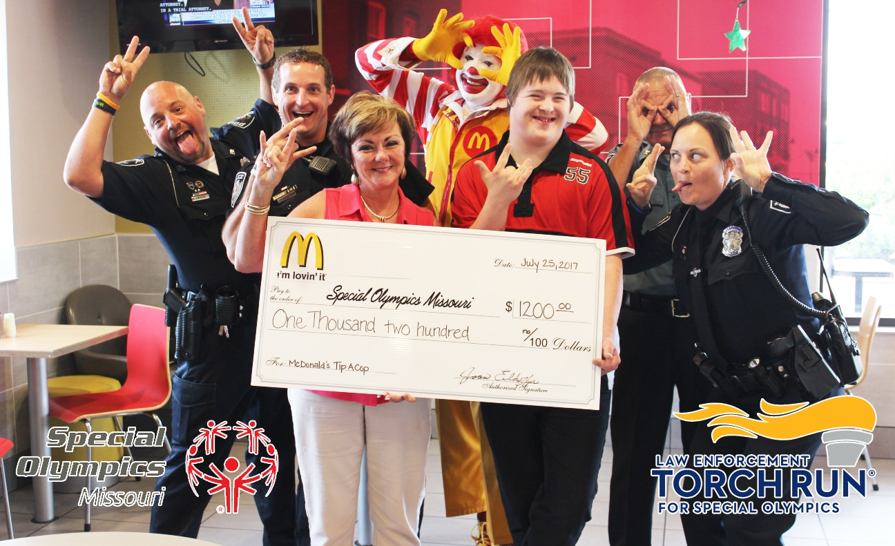 An athlete poses for a photo with law enforcement officers while holding a oversized check from McDonald's