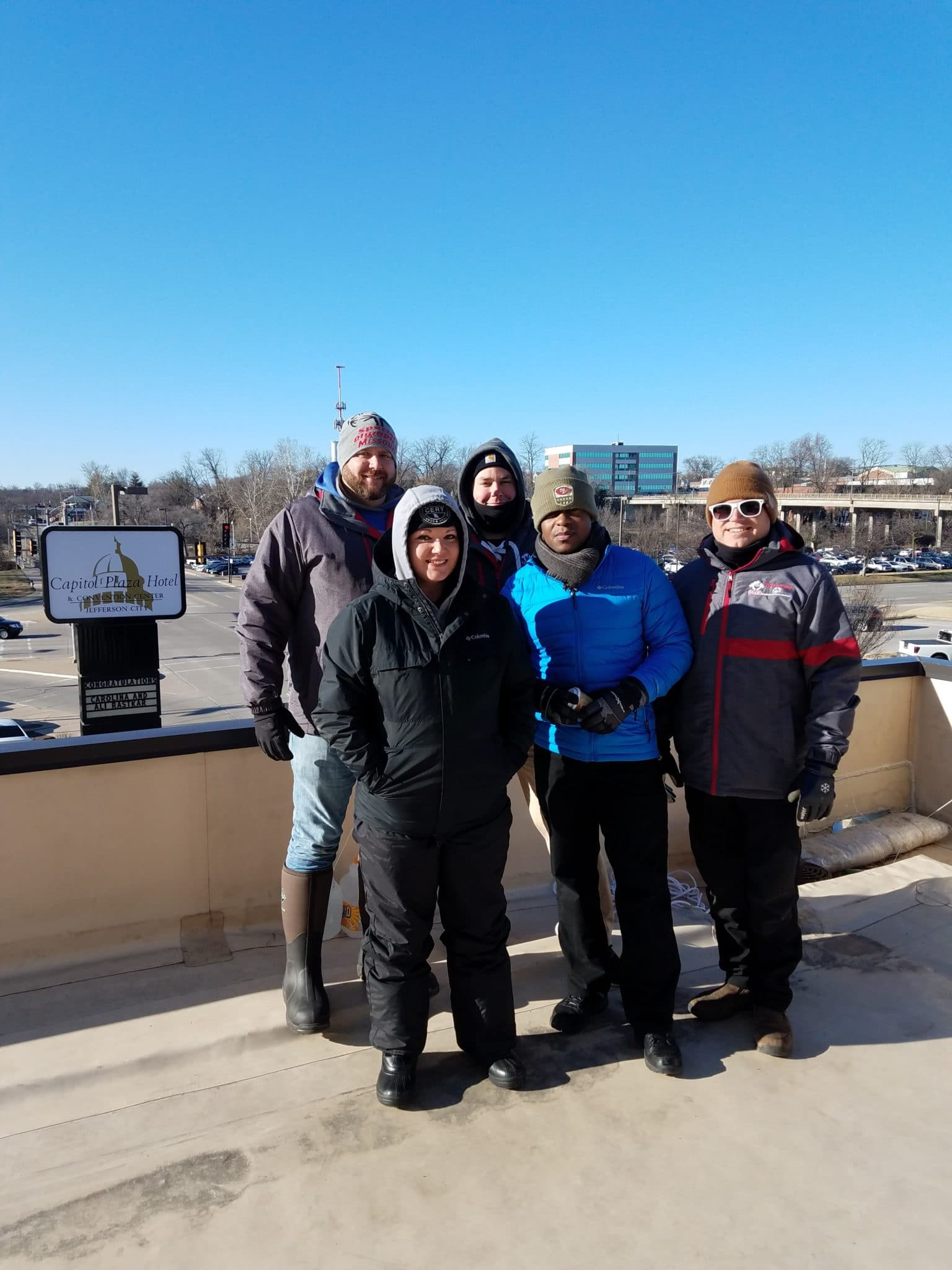 A group of people bundled up in winter clothes stand on top of a hotel roof