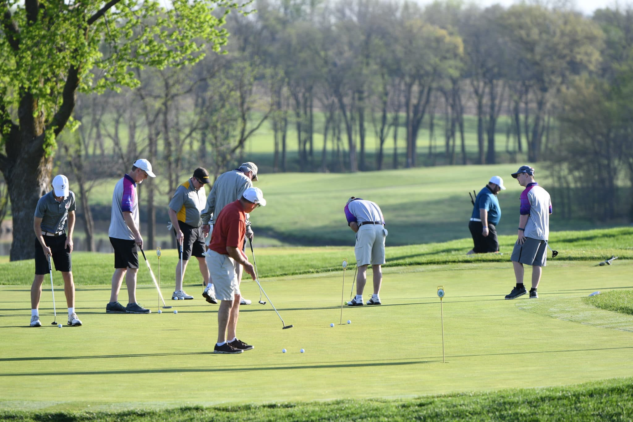 A group of golfers practice putting on a green