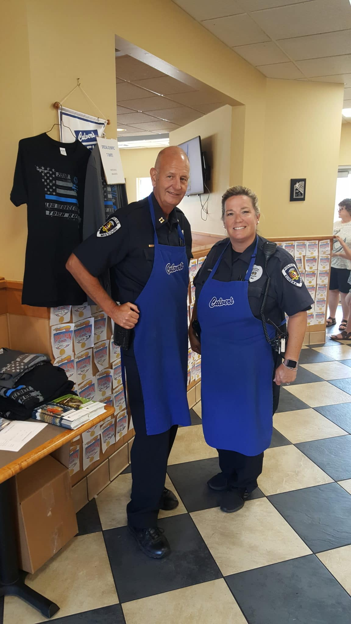 Two law enforcement officers pose for a photo while wearing Culver's aprons
