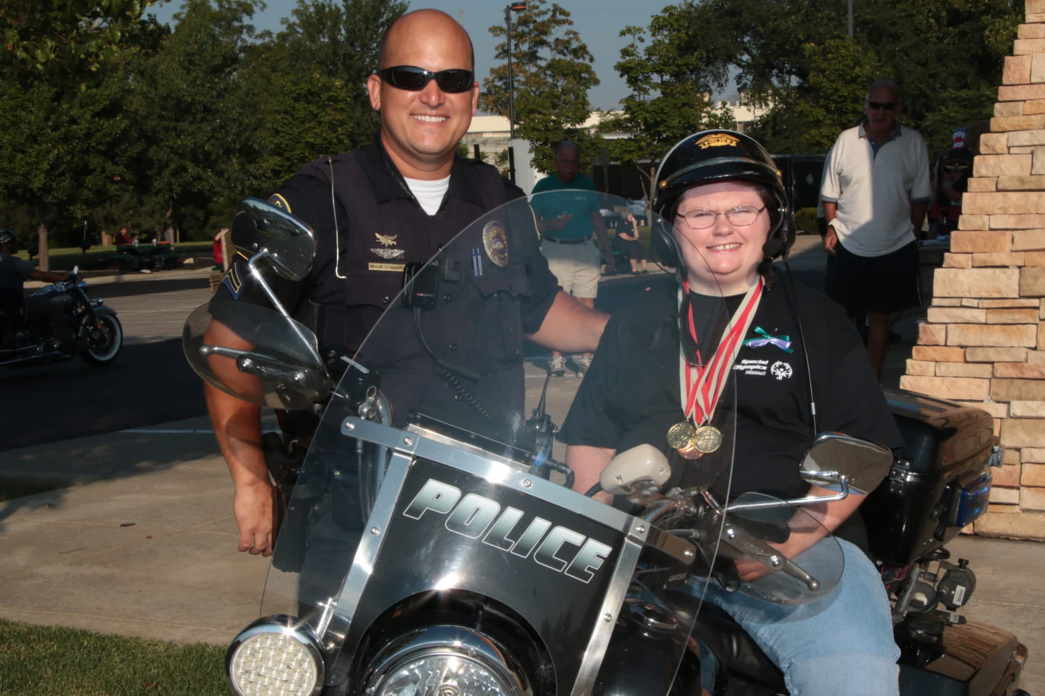 An athlete sits on a motorcycle and poses for a photo with a law enforcement officer