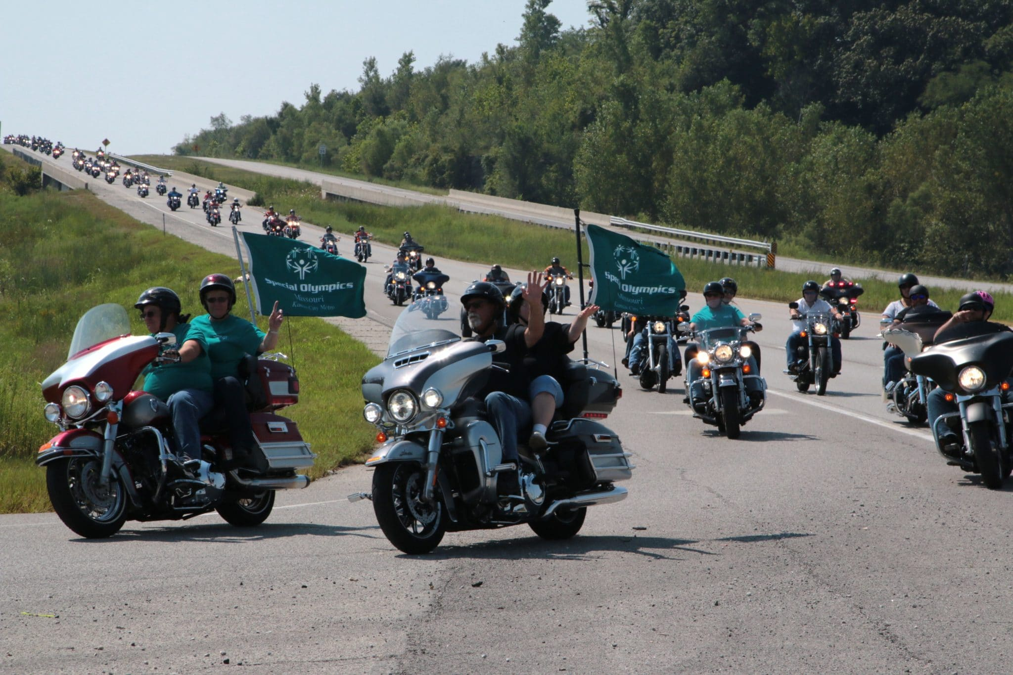 A group of more than 50 motorcycles, some with SOMO flags waving in the wind, travel down the street