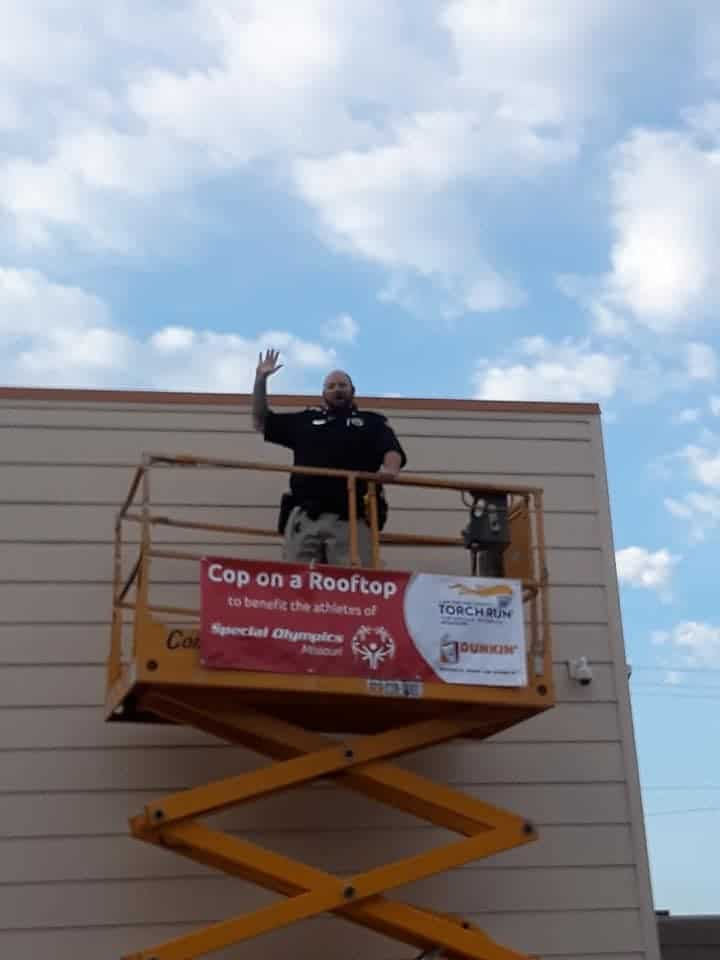 A law enforcement officer stands on a lift outside of a Dunkin' Donuts